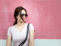 Beautiful Asian woman in sunglasses in a city over pink wall background royalty free stock photos