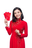 Portrait of a beautiful Asian woman on traditional festival cost. Ume Ao Dai holding red pocket - lucky money. Tet holiday. Lunar New Year Stock Photos