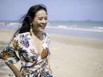 Beautiful asian woman wearing bohemian clothing style with pineapple earrings smiling with freshness face walking on the beach royalty free stock photo
