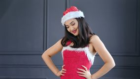 Portrait of beautiful Asian woman wearing Santa Claus hat and suit smiling and posing at studio. In gray background. Attractive happy Christmas Korean young