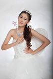 Portrait beautiful asian woman in white wedding dress with fairy scepter with angel wings Stock Photos