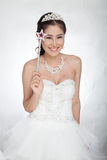 Portrait beautiful asian woman in white wedding dress with fairy scepter with angel wings. Smiling in studio light ,white background Stock Photo