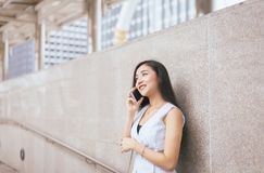 Portrait beautiful asian woman using mobile phone and walking in the center city,Happy and smiling,Female with positive attitude. Portrait beautiful asian young royalty free stock images