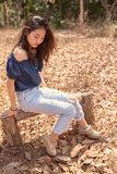 Portrait of beautiful asian younger woman sitting on wood bench. With dry tree leaves on the ground stock photos