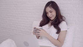 Portrait of beautiful attractive Asian woman using computer or laptop holding a warm cup of coffee or tea while lying on the bed. stock video