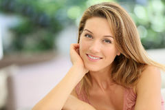 Portrait of a beautiful attractive middle-aged woman sitting outside Royalty Free Stock Image