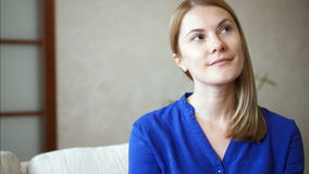 Portrait of beautiful attractive young woman in blue blouse sitting on sofa in living room smiling. Portrait of beautiful attractive young woman in dark blue stock footage
