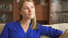 Portrait of beautiful attractive young woman in blue blouse sitting on sofa in living room thinking. Portrait of beautiful attractive young woman in dark blue stock video