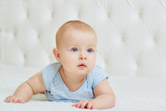Portrait of beautiful baby boy on a white bed. The child with bl Royalty Free Stock Photography