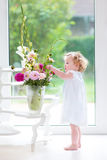 Portrait of a beautiful baby girl with fresh flowers Stock Image