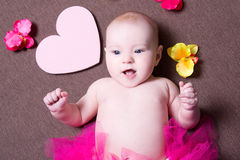 Portrait of beautiful baby girl in pink skirt lying with hearts Royalty Free Stock Photography