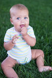 Portrait of beautiful baby girl sitting in grass Stock Photography