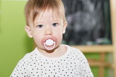 Portrait of a beautiful baby with pacifier in the mouth Stock Images