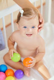 Portrait of a beautiful baby sitting in the crib.  Stock Image