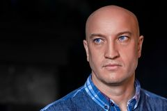 Portrait of a beautiful bald man with blue eyes stock image