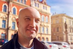 Portrait of a beautiful bald man who smiles at the background of the house, the color of instagram stock photo