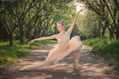 Portrait of beautiful ballerina with romantic and tender emotion. Young woman with perfect body in white tutu dancing in the green landscape. Beautiful ballerina Royalty Free Stock Image