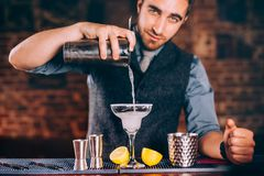 Portrait of beautiful bartender using bar tools for alcoholic cocktails. Margarita with tequila, slice of lemon and ice royalty free stock image