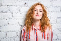 Portrait of a beautiful beautiful young woman student with red curly hair and freckles on her face is leaning against a brick wall. Of gray color. Dressed in a royalty free stock photo