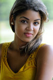 Portrait of a beautiful biracial woman. Beautiful young biracial woman - outdoor portrait wearing a yellow blouse royalty free stock photos