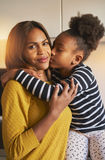 Portrait of beautiful black family. Mom and daughter, kissing and love stock photo