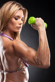 Portrait of beautiful blond bodybuilder holding green dumbbell. Royalty Free Stock Photos