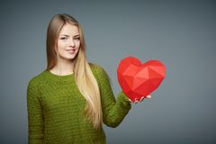 Portrait of beautiful blond girl holding heart shape royalty free stock photos