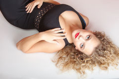 Portrait beautiful blond girl make up lying on floor studio shot Royalty Free Stock Image