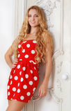 Portrait of the beautiful blond girl in polka dots dress in livi Stock Photo
