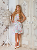 Portrait of the beautiful blond girl in polka dots dress. In living room stock images