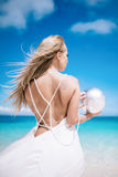 Portrait of the beautiful blond long hair bride in a open back wedding dress stand on the white sand beach with a pearl. Looking t royalty free stock image