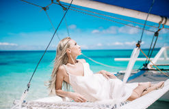Portrait of the beautiful blond long hair bride in white dress. She lay on the blue sailboat. Blue sky and turquoise se royalty free stock images
