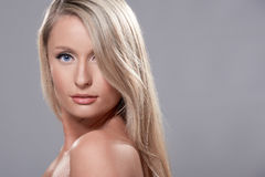 Portrait of beautiful blond model with blue eyes, on grey backgr Royalty Free Stock Image
