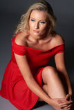 Portrait of beautiful blond model with blue eyes in red dress, o Royalty Free Stock Images
