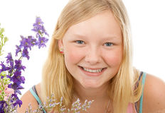 Portrait of Beautiful Blond Teenage Girl. Portrait of a beautiful blond, blue-eyed teenage girl with flowers, on a white background Royalty Free Stock Images