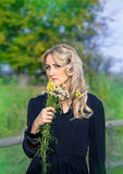 Portrait of beautiful blond woman with bouquet of bright wildflo Stock Photos