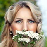 Portrait of beautiful blond woman with bouquet of bright wildflo Royalty Free Stock Photo