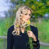 Portrait of beautiful blond woman with bouquet flowers Stock Photography