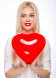 Portrait of Beautiful blond woman with bright makeup and red heart in hand. valentines day Royalty Free Stock Image