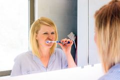 Portrait of a beautiful blond woman brushing teeth royalty free stock photos