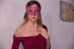 Blonde girl with fuchsia carnival mask over white background. Masquerade. Portrait of Beautiful Blond Woman in a Carnival Mask. Masquerade. Girl. Beauty royalty free stock photo
