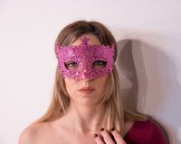 Blonde girl with fuchsia carnival mask over white background. Masquerade. Portrait of Beautiful Blond Woman in a Carnival Mask. Masquerade. Girl. Beauty royalty free stock photography