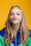 Portrait of beautiful blond woman in casual colorful vivid clothes making mustache with her hair royalty free stock photos