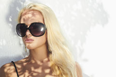 Portrait of beautiful blond woman.girl in sunglasses near the wall Royalty Free Stock Photos