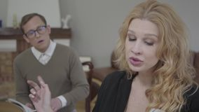 Portrait of beautiful blond woman reading aloud the book in the foreground while modestly dressed man looking at the stock video