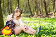 Portrait of a beautiful blond woman relaxing with guitar under tree Royalty Free Stock Photography
