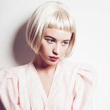 Portrait of a beautiful blond woman with short hair in the studio on a white background royalty free stock image