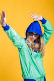 Portrait of beautiful blond woman in sunglasses and blue green hooded jacket on yellow background. hipster summer. Stock Photography