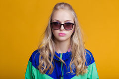 Portrait of beautiful blond woman in sunglasses and blue green hooded jacket on yellow background. hipster summer. Stock Image