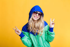 Portrait of beautiful blond woman in sunglasses and blue green hooded jacket on yellow background. hipster summer. Stock Photos